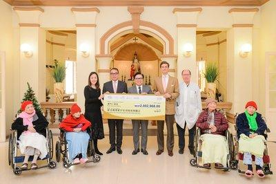Sands China President Dr. Wilfred Wong (standing centre) and Vice President of Corporate Communications and Community Affairs Winnie Wong (standing left) present a MOP 2 million cheque to Macau Holy House of Mercy President Antonio Jose de Freitas (standing second from left) and other representatives Tuesday at Macau Holy House of Mercy's elderly home. The donation will help cover the costs of repairing the elderly home, which was heavily damaged during Typhoon Hato.