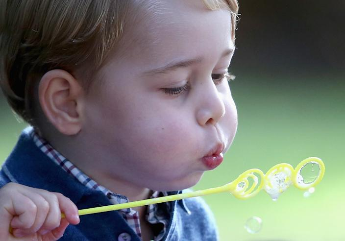 Playing with bubbles at a party in Canada in 2016, soon after his third birthday. (Getty Images)