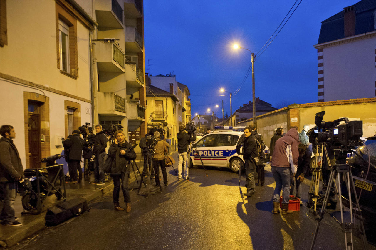 Journalists gather near by as French police secure the area where they exchanged fire and were negotiating with a gunman who claims connections to al-Qaida and is suspected of killing three Jewish schoolchildren, a rabbi and three paratroopers, Wednesday, March 21, 2012 in Toulouse, southwestern France. The suspect is 24 years old, of French nationality and was known to authorities for having spent time in Afghanistan and Pakistan. (AP Photo/Bruno Martin)