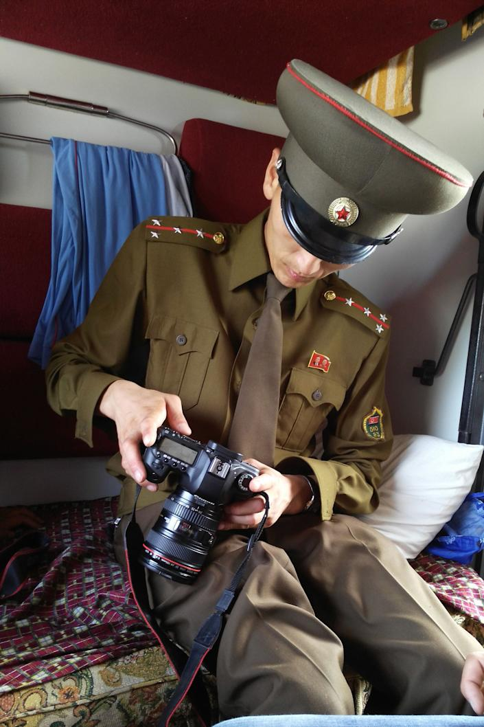 A customs officer checks a passenger's camera on a train from Moscow to Pyongyang at the Tumangang railway station.