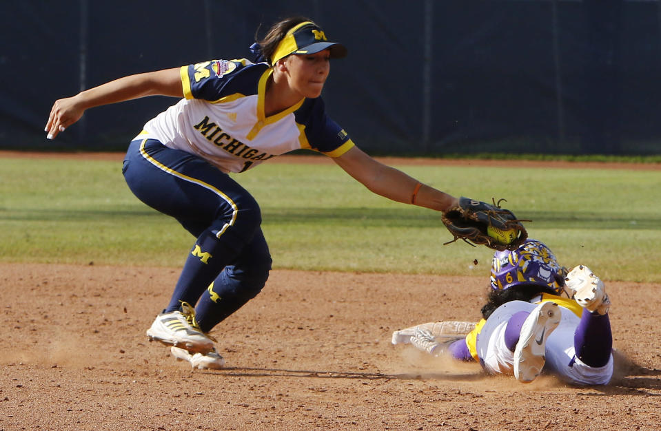 Michigan's Abby Ramirez, left, tags out LSU's A.J. Andrews, right, during the sixth inning of an NCAA Women's College World Series softball game in Oklahoma City, Sunday, May 31, 2015. Michigan won 6-3 and moves on to the championship series. (AP Photo/Alonzo Adams)