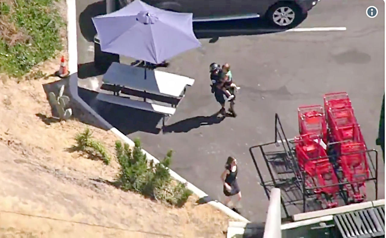 <p>A Los Angeles Police officer carries a child as another runs ahead of him after a pursuit, and the driver ran into a nearby Trader Joe's supermarket, starting a hostage situation in the Silverlake district of Los Angeles Saturday. (Photo: KNBC-TV via AP) </p>