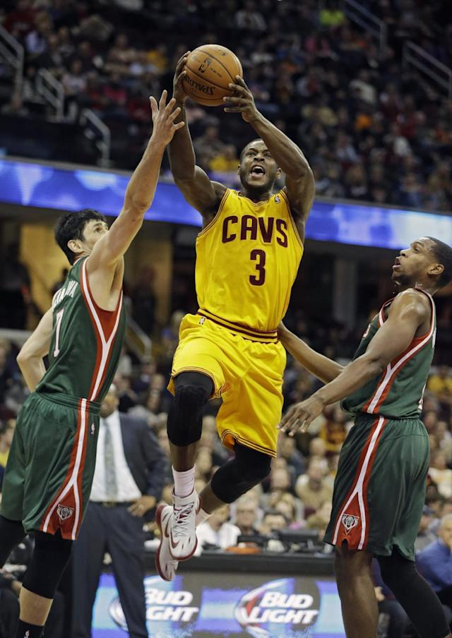 Cleveland Cavaliers' Dion Waiters (3) goes up for a shot between Milwaukee Bucks' Ersan Ilyasova, left, and Khris Middleton in the second quarter of an NBA basketball game, Friday, Jan. 24, 2014, in Cleveland. (AP Photo/Mark Duncan)