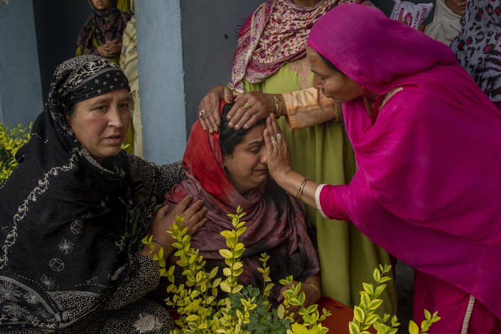 A Kashmiri villager cries beside her home that was destroyed in a gunfight after suspected rebels took refuge in it, in Pulwama, south of Srinagar, Indian controlled Kashmir, Wednesday, July 14, 2021. Three suspected rebels were killed in a gunfight in Indian-controlled Kashmir on Wednesday, officials said, as violence in the disputed region increased in recent weeks. Two residential houses were also destroyed. (AP Photo/ Dar Yasin)
