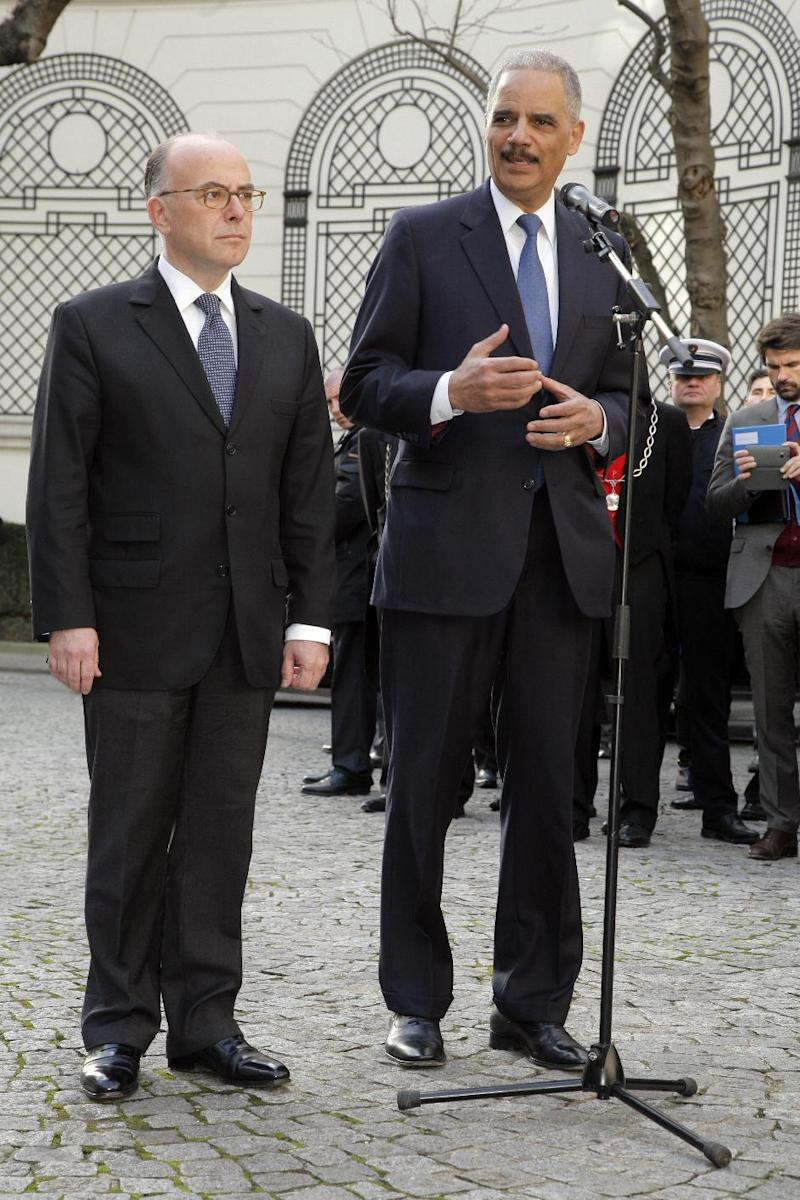 US Attorney General Eric Holder (R) speaks to the press next to French Interior Minister Bernard Cazeneuve after their International meeting against terrorism at the Interior Ministry in Paris on January 11, 2015
