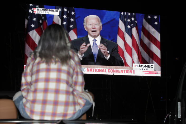 Eva Morales watches Democratic presidential candidate former Vice President Joe Biden speak, during the final day of the Democratic National Convention, Thursday, Aug. 20, 2020, on a screen at a drive-in theater watch party during the final night of the Democratic National Convention, Thursday, Aug. 20, 2020, in Washington. (AP Photo/Luis M. Alvarez)