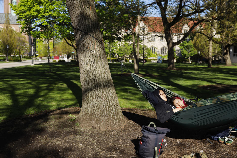 University of Chicago sophomore Silvana Montagu, right and Sonny Lee take advantage of warm spring weather as they spend time in a hummock Thursday, May 6, 2021, in University of Chicago. Even as restrictions relax across much of the United States, colleges and universities have taken new steps to police campus life as the virus spreads through students who are among the last adults to get access to vaccines. (AP Photo/Shafkat Anowar)