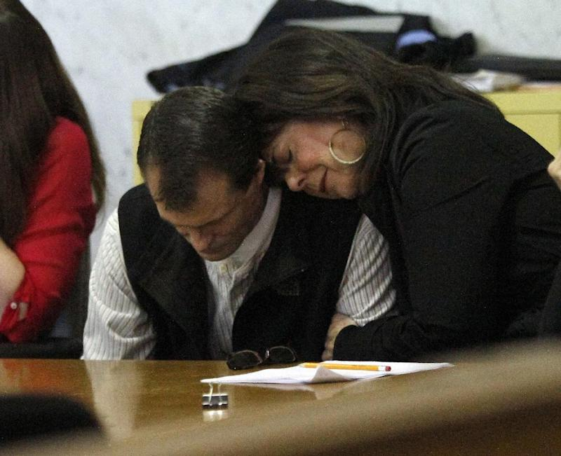 William Coultas, left, is comforted by Christine Schwanenberg after a verdict is reached regarding a 2008 helicopter crash that killed 8 firefighters and the pilot in Portland, Ore., Tuesday, March 27, 2012.  Coultas is the surviving co-pilot while Schwanenberg's husband, who was the pilot, was killed.  The jury ruled that a problem with an engine was responsible for the crash in Northern California. and awarded a verdict against General Electric for $177 million.  (AP Photo/Don Ryan)
