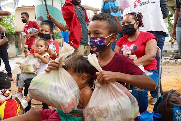 Families sit or walk around, some holding plastic bags of donated goods