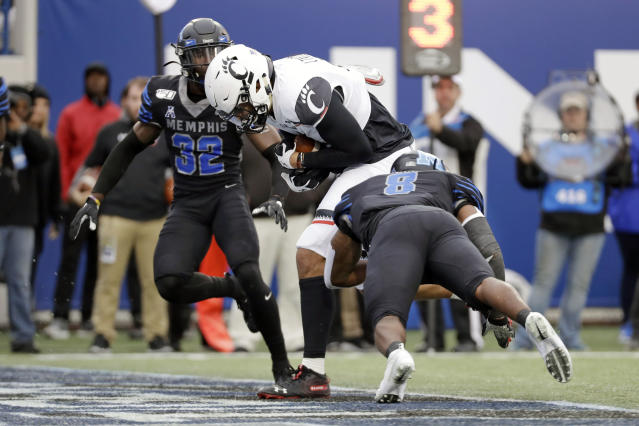 Cincinnati tight end Leonard Taylor, center, gets into the end zone past Memphis defenders Jacobi Francis (32) and Xavier Cullens (8) for a touchdown in the first half of an NCAA college football game Friday, Nov. 29, 2019, in Memphis, Tenn. (AP Photo/Mark Humphrey)