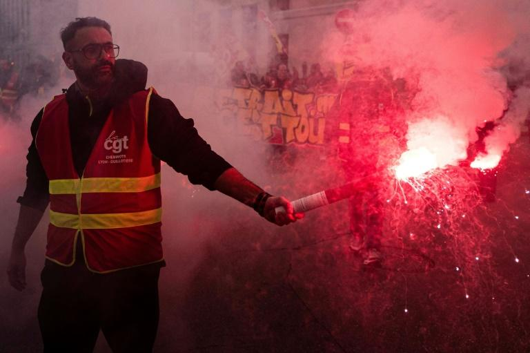 A protester wearing a gilet of the moderate CGT union brandishes a smoke bomb during Friday's demonstration in Lyon, southeast France (AFP Photo/ROMAIN LAFABREGUE)
