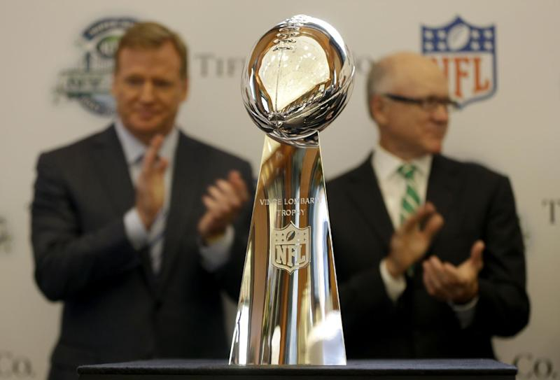 NFL Commissioner Roger Goodell, left, and New York Jets owner Woody Johnson clap as the Vince Lombardi Trophy is presented during a news conference at Tiffany & Co. in New York, Wednesday, Sept. 4, 2013. The retrieval of the trophy from Tiffany & Co. is one of many events leading up to the Super Bowl in New Jersey on Feb. 2, 2014. (AP Photo/Seth Wenig)