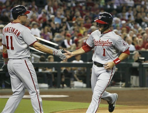Washington Nationals' Steve Lombardozzi, right, is congratulated by teammate Ryan Zimmerman (11) after scoring against the Arizona Diamondbacks on a sacrifice-fly by Bryce Harper during the third inning of a baseball game on Friday, Aug. 10, 2012, in Phoenix. (AP Photo/Ralph Freso)