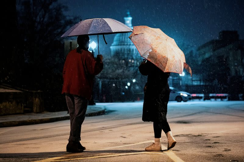 FILE PHOTO: Women watch the snow fall on Capitol Hill in Washington