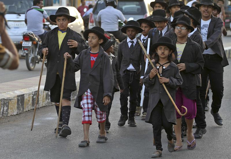 Young supporters of the Charlie Circle, a Charlie Chaplin fan-club, participate in an annual parade to celebrate the birthday of Charlie Chaplin in Adipur, Gujarat state, India, Tuesday, April 16, 2013. Canes in hand and bowler hats firmly in place, dozens of Charlie Chaplin impersonators tramped through the streets of this small port town in western India on Tuesday to celebrate the birthday of the legendary comic actor and filmmaker. (AP Photo/Ajit Solanki)