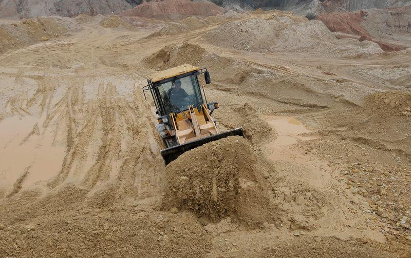 FILE PHOTO: A labourer operates a bulldozer at a site of a rare earth metals mine at Nancheng county, Jiangxi province