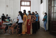 Employees of Colombo municipal council wait to give their swab samples to test for COVID-19 in Colombo, Sri Lanka, Wednesday, Oct. 7, 2020. Authorities in Sri Lanka on Wednesday widened a curfew and warned of legal action against those evading treatment for COVID-19 after reporting an escalating cluster centered around a garment factory in the capital's suburbs. (AP Photo/Eranga Jayawardena)