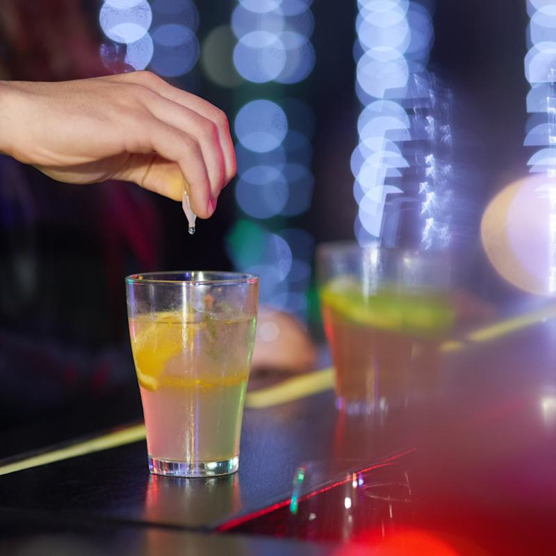 Closeup shot of a man drungs into a drink in a nightclub