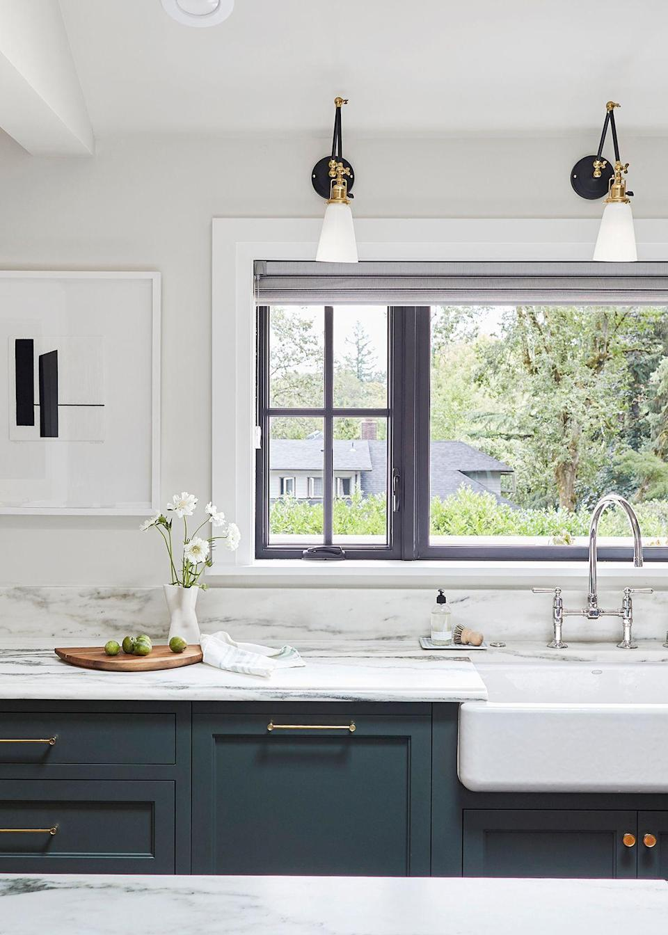 """But let's talk about the color palette because this kitchen really hits a home run in that department. """"I've done a lot of blue kitchens so I wanted to do something different here,"""" says Henderson. In general, they stayed away from gray throughout the home because as Henderson puts it, """"Portland is already so gray so often."""" After testing a million shades of green, they eventually landed on the pewter green. """"I'm so happy with it,"""" exclaimed Henderson. """"It's deep, saturated, milky, and dramatic. It makes a quiet statement. It is a bold color without feeling bold, and it gives a lot of life to the room while keeping it timeless and traditional."""""""