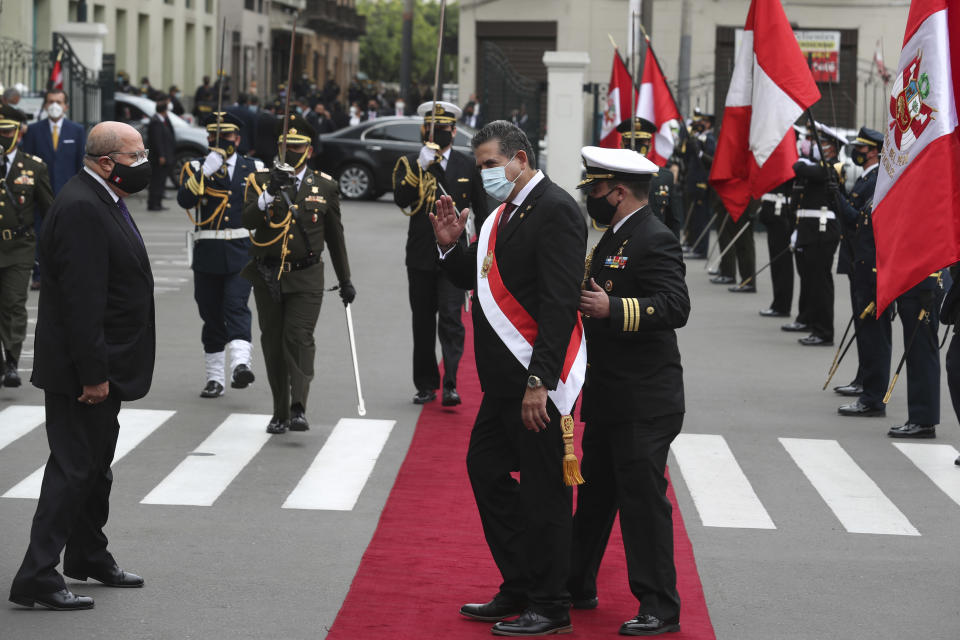 A military aide shows the way to Manuel Merino, the head of Peru's legislature, after he was sworn-in as Peru's new president, replacing Martín Vizcarra who was removed by lawmakers the previous night, in Lima Peru, Tuesday, Nov. 10, 2020. Congress voted to oust Vizcarra over his handling of the new coronavirus pandemic and unproven allegations of corruption years ago. (AP Photo/Martin Mejia)
