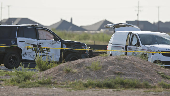 A city of Odessa police car, left, and a U.S. mail vehicle, right, which were involved in Saturday's shooting, are pictured outside the Cinergy entertainment center, Sunday, Sept. 1, 2019, in Odessa, Texas. The death toll in the West Texas shooting rampage increased Sunday as authorities investigated why a man stopped by state troopers for failing to signal a left turn opened fire on them and fled, shooting over a dozen people as he drove before being killed by officers outside a movie theater. (AP Photo/Sue Ogrocki)