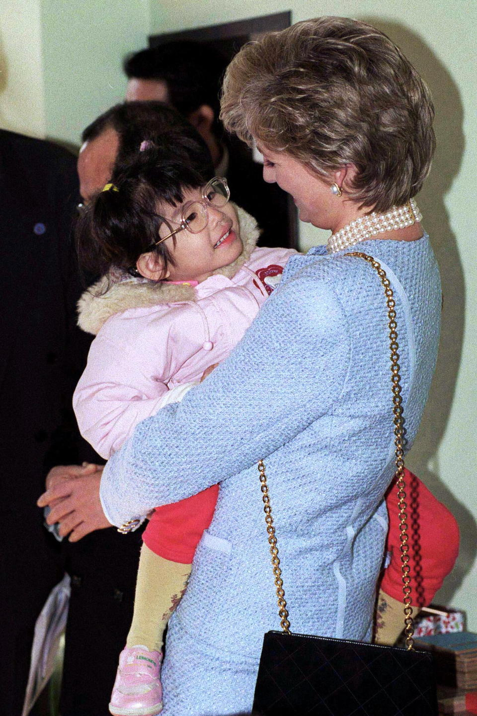 Princess Diana, pictured holding a child in Tokyo in 1995, was known as the 'People's Princess'. [Photo: Getty]