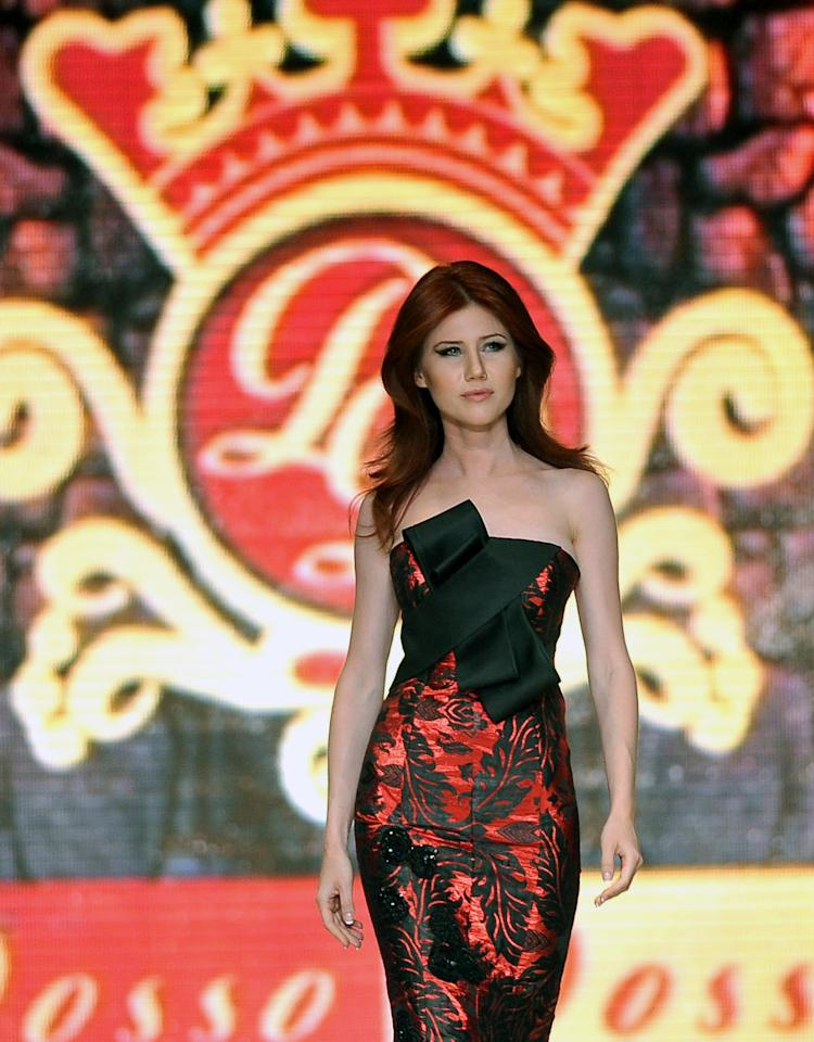 In this photo taken Friday, June 8, 2012, Russian ex-spy Anna Chapman walks a Turkish catwalk at a fashion show in Antalya, Turkey. The 30-year-old Chapman was deported from the United States in 2010 along with nine other Russian sleeper agents. (AP Photo)