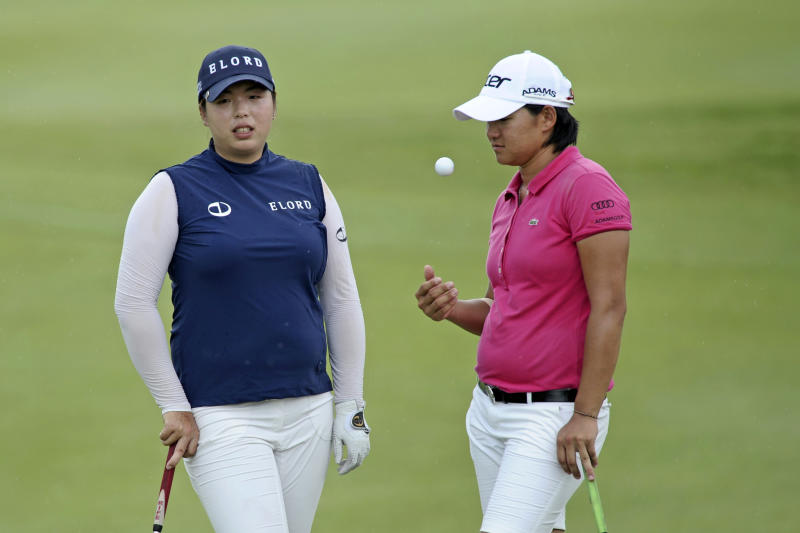 China's China's Shanshan Feng, left, and Yani Tseng of Taiwan stand on the 17th green during the final round of the HSBC Women's Champions golf tournament Sunday, Feb. 26, 2012 in Singapore. (AP Photo/Joseph Nair)