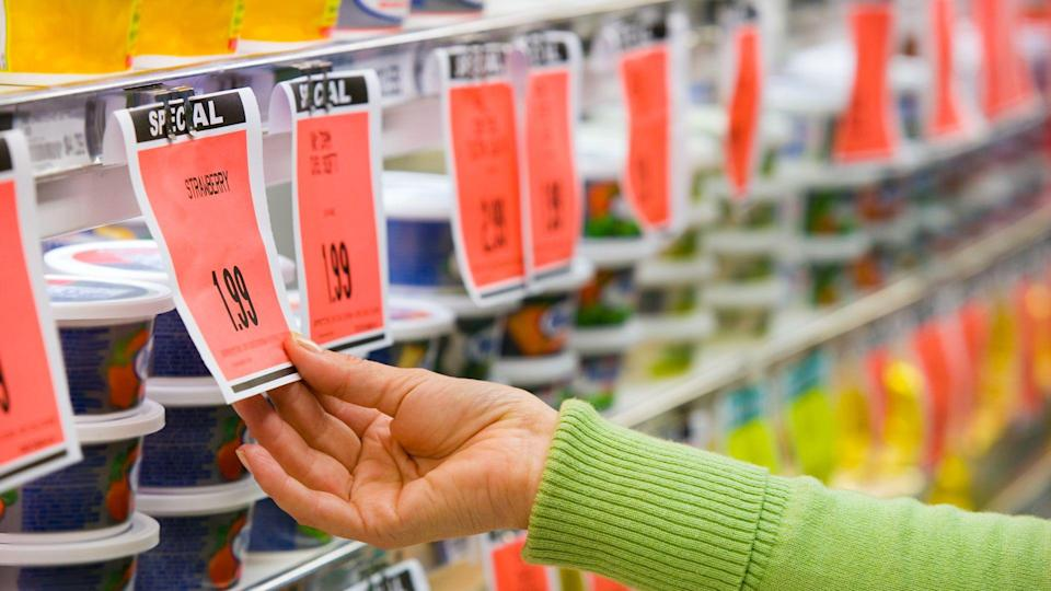 Checking price of item in supermarket aisle.