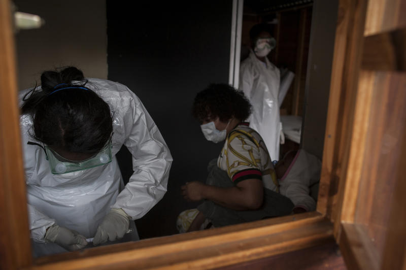 In this photo taken Friday, April 3, 2020 medical workers prepare to test a person, centre, for COVID-19 in a mobile testing unit in Yeoville, Johannesburg's. South Africa, one of the world's most unequal countries with a large population vulnerable to the new coronavirus, may have an advantage in the coronavrius outbreak, honed during years battling HIV and tuberculosis: the know-how and infrastructure to conduct mass testing. (AP Photo/Shiraaz Mohamed)