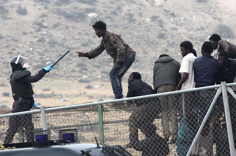 A sub-Saharan migrant agues with a Spanish Guardia Civil officer holding a baton, as they sit on top of a metallic fence that divides Morocco and the Spanish enclave of Melilla, Thursday, May 1, 2014. Spain says around 700 African migrants have rushed its barbed wire border fences in the North African enclave of Melilla, and although police repelled most, 140 managed to enter Spanish territory. The migrants charged the fences in two waves, with 500 arriving in the early hours and another 200 later Thursday morning. Spain and Morocco stepped up border vigilance in Feb. when 15 migrants drowned trying to enter Spain's other north African coastal enclave, Ceuta. (AP Photo/Fernando Garcia)