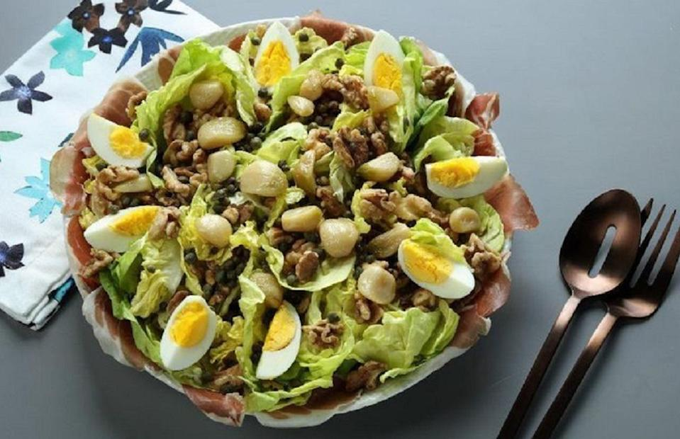 """<p>As the name implies, this salad is heavenly. The components of the dish on their own are enough to turn heads (walnuts, lettuce, prosciutto, eggs), but the addition of the buttery-soft garlic cloves and garlic oil really tie it all together.</p> <p><a href=""""https://www.thedailymeal.com/recipes/hand-of-god-salad?referrer=yahoo&category=beauty_food&include_utm=1&utm_medium=referral&utm_source=yahoo&utm_campaign=feed"""" rel=""""nofollow noopener"""" target=""""_blank"""" data-ylk=""""slk:For the Hand of God Salad recipe, click here."""" class=""""link rapid-noclick-resp"""">For the Hand of God Salad recipe, click here.</a></p>"""