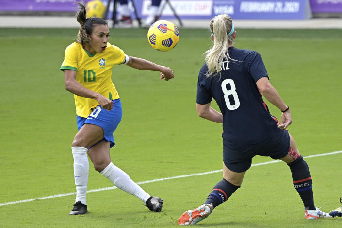 United States midfielder Julie Ertz (8) blocks a shot on goal by Brazil midfielder Marta (10) during the first half of a SheBelieves Cup women's soccer match, Sunday, Feb. 21, 2021, in Orlando, Fla. (AP Photo/Phelan M. Ebenhack)