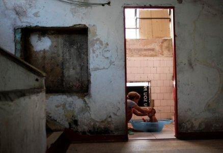A woman bathes a baby in a communal bathroom at the abandoned Prestes Maia textile factory occupied by a homeless movement in downtown Sao Paulo, Brazil, May 10, 2018. REUTERS/Nacho Doce