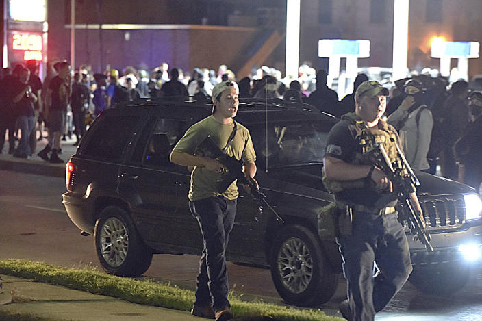 Kyle Rittenhouse, at left in backwards cap, walks along Sheridan Road in Kenosha, Wis., at around 11 p.m. Tuesday, Aug. 25, 2020, with another armed civilian Tuesday night. (Adam Rogan/The Journal Times via AP)