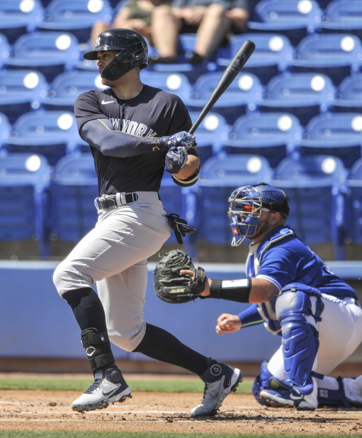 Toronto Blue Jays catcher Alejandro Kirk, right, looks on as New York Yankees' Giancarlo Stanton hits a single off Toronto starter Thomas Hatch during the first inning of a spring training baseball game Wednesday, March 17, 2021, at TD Ballpark in Dunedin, Fla. (Steve Nesius/The Canadian Press via AP)
