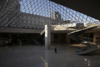 A man walks through the deserted Louvre museum, in Paris, Thursday, Feb. 11, 2021. It's uncertain when the Louvre will reopen, after being closed on Oct. 30 in line with the French government's virus containment measures. But those lucky enough to get in benefit from a rarified private look of collections covering 9,000 years of human history -- with plenty of space to breathe. (AP Photo/Thibault Camus)