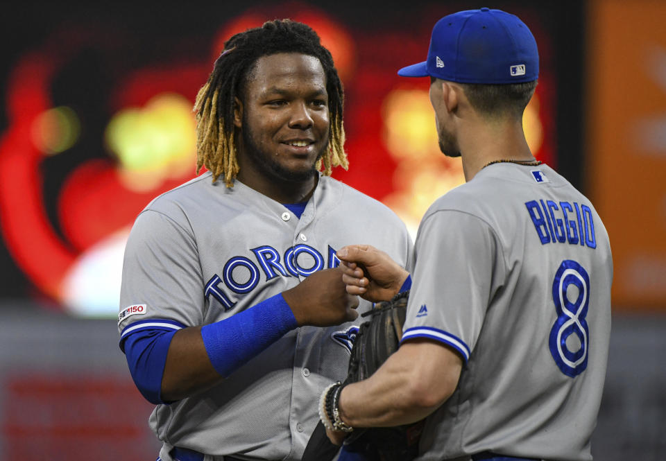 BALTIMORE, MD - JUNE 12: Toronto Blue Jays third baseman Vladimir Guerrero Jr. (27) fist pumps with second baseman Cavan Biggio (8) after the third inning during the game between the Toronto Blue Jays and the Baltimore Orioles on June 12, 2019, at Orioles Park at Camden Yards in Baltimore, MD.  (Photo by Mark Goldman/Icon Sportswire via Getty Images)