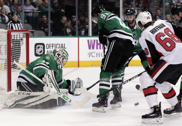 Dallas Stars goalie Kari Lehtonen, left, of Finland, and center Tyler Seguin (91) defend against pressure from Ottawa Senators left wing Mike Hoffman (68) in the second period of an NHL hockey game in Dallas, Monday, March 5, 2018. (AP Photo/Tony Gutierrez)