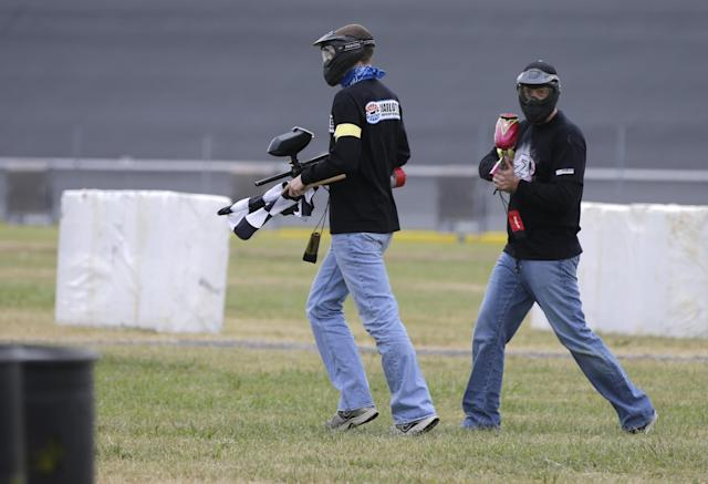 NASCAR driver Kyle Busch, right, protects one of his teammates as they carry the flag to the finish during a paintball game against members of the media at Charlotte Motor Speedway in Concord, N.C., Tuesday, Sept. 24, 2013, promoting the upcoming Bank of America 500 NASCAR Sprint Cup auto race on Oct. 12, 2013. (AP Photo/Chuck Burton)