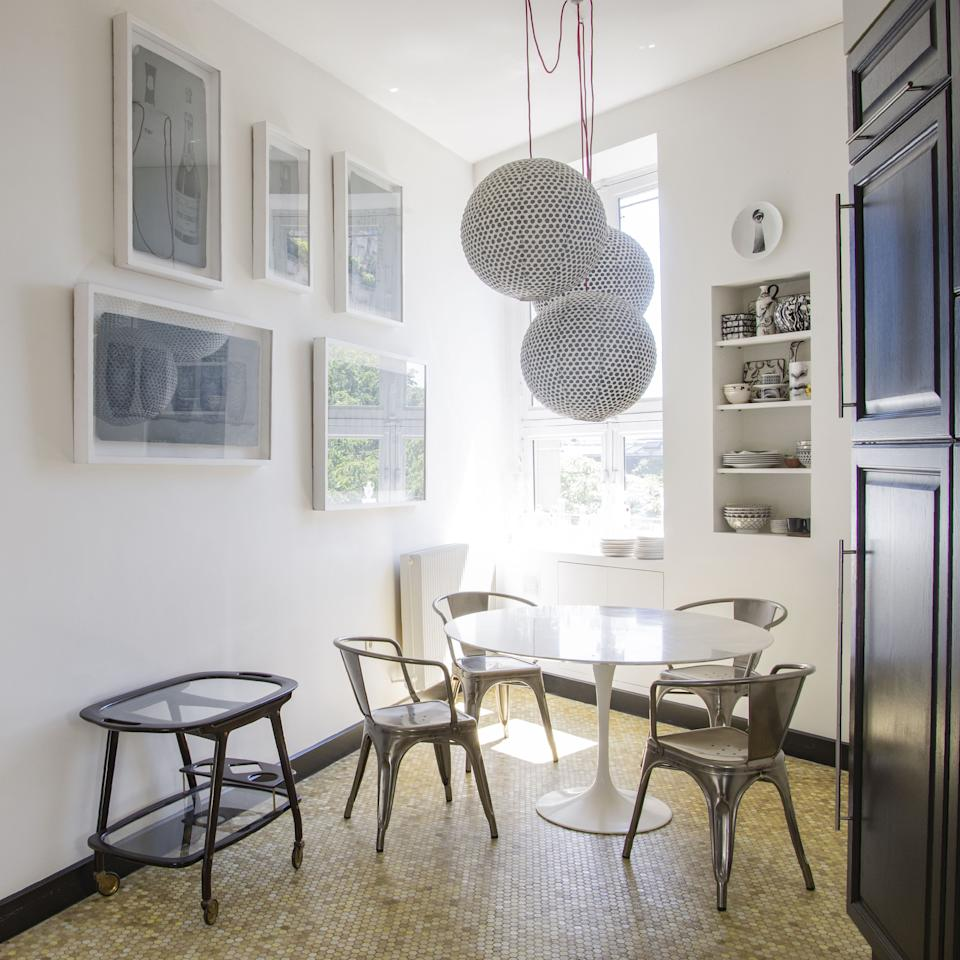 """<div class=""""caption""""> The kitchen table is <a href=""""https://www.knoll.com/"""" rel=""""nofollow noopener"""" target=""""_blank"""" data-ylk=""""slk:Knoll"""" class=""""link rapid-noclick-resp"""">Knoll</a> and the chairs are <a href=""""https://www.tolix.com/en/node/96"""" rel=""""nofollow noopener"""" target=""""_blank"""" data-ylk=""""slk:Tolix"""" class=""""link rapid-noclick-resp"""">Tolix</a>. The vintage trolley is Italian from the 1950s, and on the wall are original zinc prints by Fornasetti. </div>"""