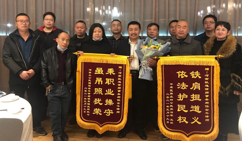 """Ren Quanniu (centre, with flowers) is presented with a banner reading """"Strong shoulders defend justice"""" by a group of villagers in Henan.€Photo: Handout"""