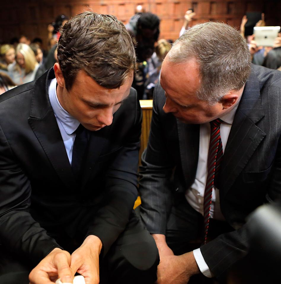 PRETORIA, SOUTH AFRICA - AUGUST 19: South African athlete Oscar Pistorius (L) speaks with his lawyer Kenny Oldwage in Pretoria Magistrates Court prior to an indictment hearing on August 19, 2013 in Pretoria, South Africa. Pistorius, 26 is accused of murdering his girlfriend Reeva Steenkamp which Pistorius denies claiming he mistook Steenkamp for an intruder. The indictment was served and the trial date of March 3, 2014 has now been set. (Photo by Jemal Countess/Getty Images)