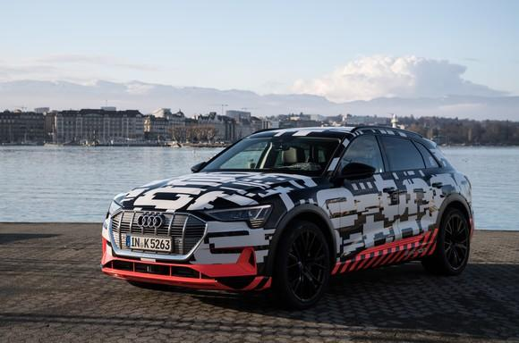 The e-tron quattro prototype, a sleek midsize SUV covered in black and white camouflage, parked on a lakefront.