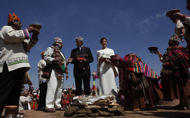 An Amauta or Aymaran spiritual guide speaks to Bolivia's Vice President Alvaro Garcia Linera, center in black, as he and his bride Claudia Fernandez, are bathed in incense smoke as other Amautas ask the Andean gods to produce good omens for the pair, in Tiwanaku, Bolivia, Saturday, Sept. 8, 2012. The ceremony uniting the 49-year-old vice president with the 25-year-old journalist was held at an ancestral site constructed by the ancient Aymara people some 3,000 years ago to observe the heavens. (AP Photo/Juan Karita)