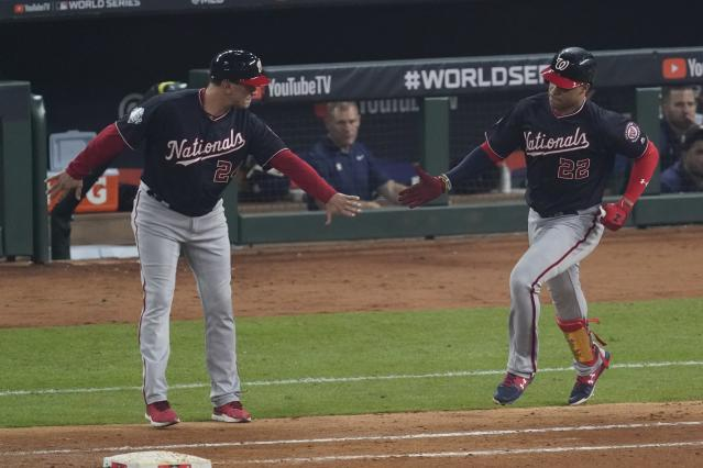 Washington Nationals' Juan Soto is congratulated by first base coach Tim Bogar after hitting a home run during the fourth inning of Game 1 of the baseball World Series against the Houston Astros Tuesday, Oct. 22, 2019, in Houston. (AP Photo/Eric Gay)