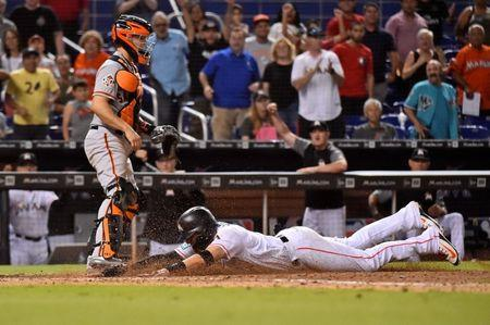 Jun 13, 2018; Miami, FL, USA; Miami Marlins shortstop Miguel Rojas (19) dives safely into home plate to score the game winning run in the ninth inning against the San Francisco Giants at Marlins Park. Mandatory Credit: Jasen Vinlove-USA TODAY Sports