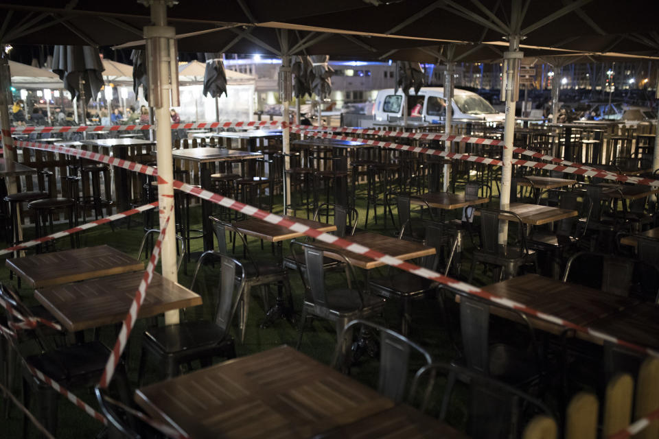 A bar terrace is cordoned off with tape in Marseille, southern France, Sunday Sept. 27, 2020. As restaurants and bars in Marseille prepared Sunday to shut down for a week as part of scattered new French coronavirus restrictions, Health Minister Olivier Veran insisted that the country plans no fresh lockdowns. (AP Photo/Daniel Cole)