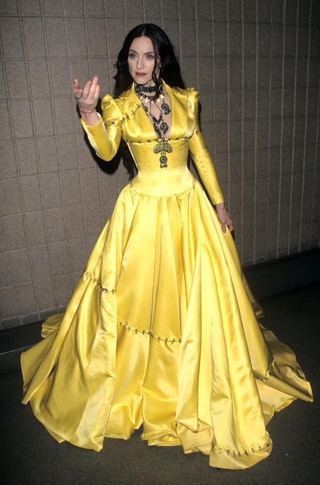 <p>This full-skirted, yellow silk dress – paired with gothic layered necklaces – was more Disney princess than Madonna. <em>[Photo: Getty]</em> </p>