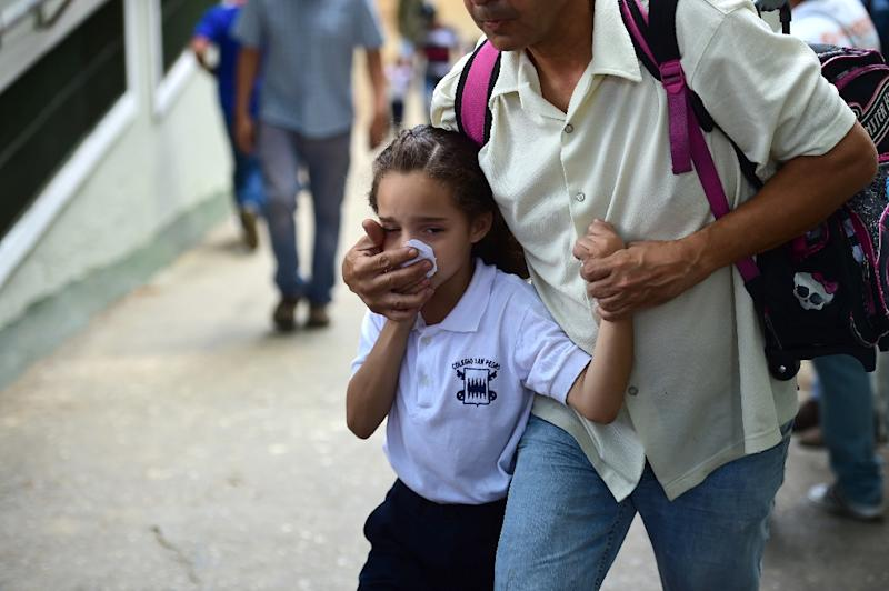 A schoolgirl covers her nose and mouth to avoid breathing tear gas shot by police at opponents of Venezuelan President Nicolas Maduro marching in Caracas on April 26, 2017 (AFP Photo/RONALDO SCHEMIDT)